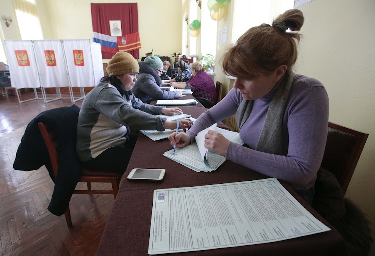Members of a local electoral commission sign ballots ahead of Russia's presidential election  in Smolensk, Russia, on March 18 2018. REUTERS