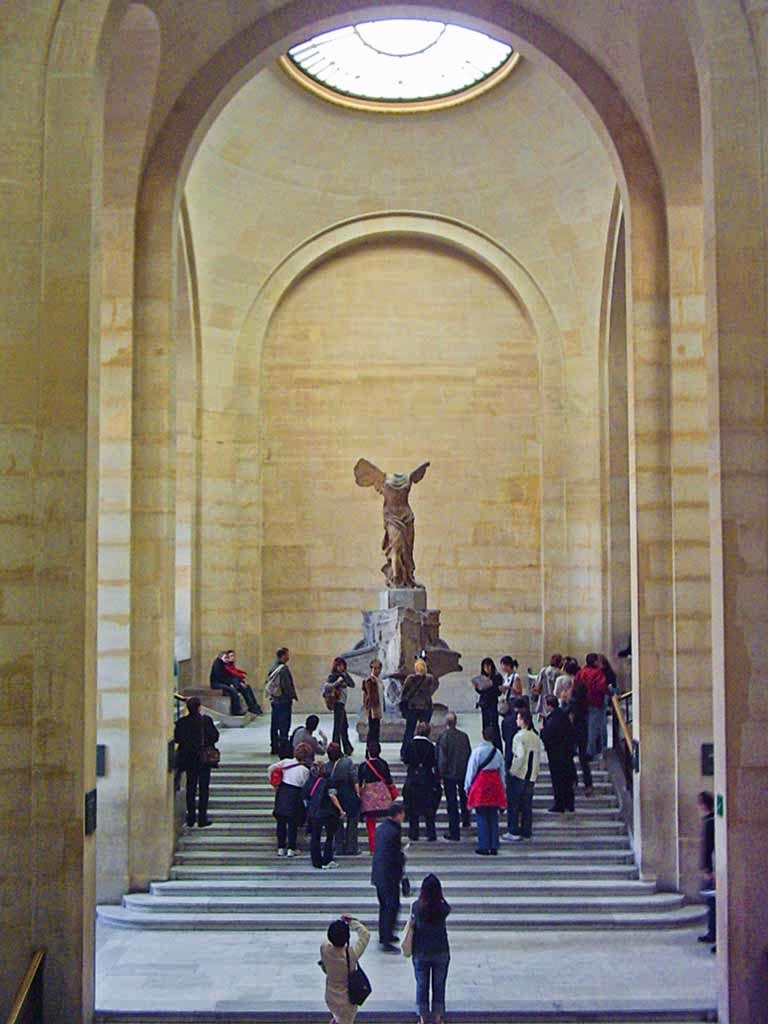 Photo: Winged Victory poses for her admirers in a Louvre stair well.