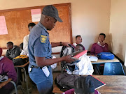 An police officer searches  pupils' school bags for drugs and weapons  at  Bhekiswayo High  in  Mpumalanga   during a  raid yesterday. /Mandla Khoza