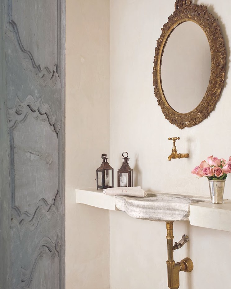 Luxurious and elegant powder room with blue antique doors, gilt mirror, and stone sink in Houston home with interior design by Pamela Pierce. #powderroom #Frenchcountry #PamelaPierce #frenchfarmhouse #stonesink