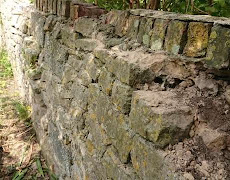 Stone wall has been repaired badly over many years