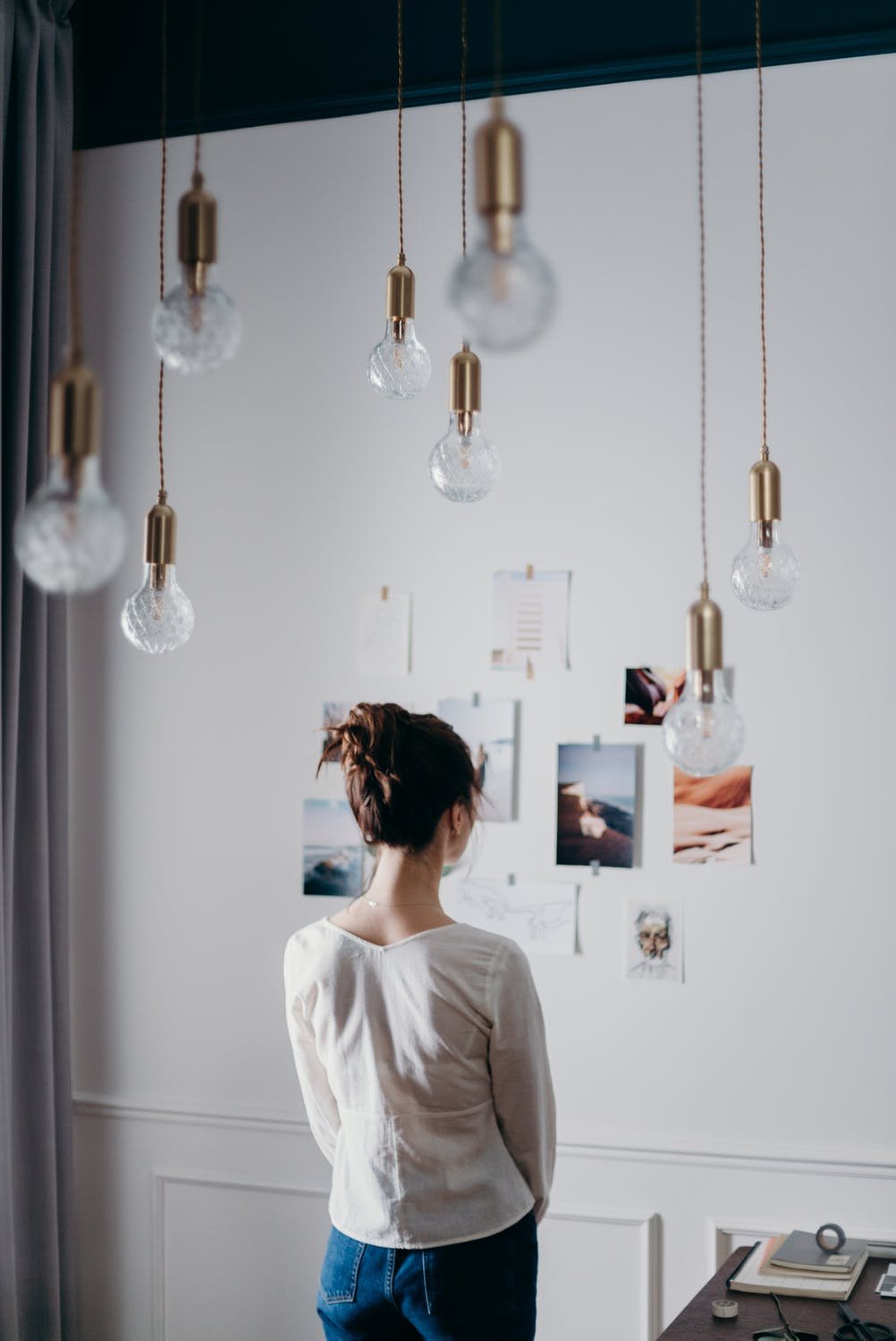 girl looking at wall with taped photos