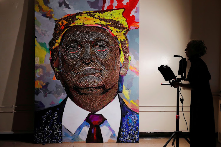 Artist Daria Marchenko attempts to adjust the lighting to properly capture a portrait of U.S. President Donald Trump made of coins and casino tokens by herself and Daniel D. Green in a classroom in New York.