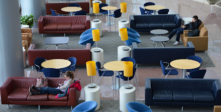 Photo: Students relax between classes in the Smeal Business Building atrium lobby of the University Park campus of Penn State.