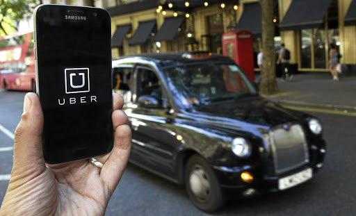 A model holds up a phone showing the Uber app, in London. Picture: REUTERS