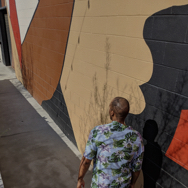 Man walking outside in an alleyway, with street art on the wall behind him