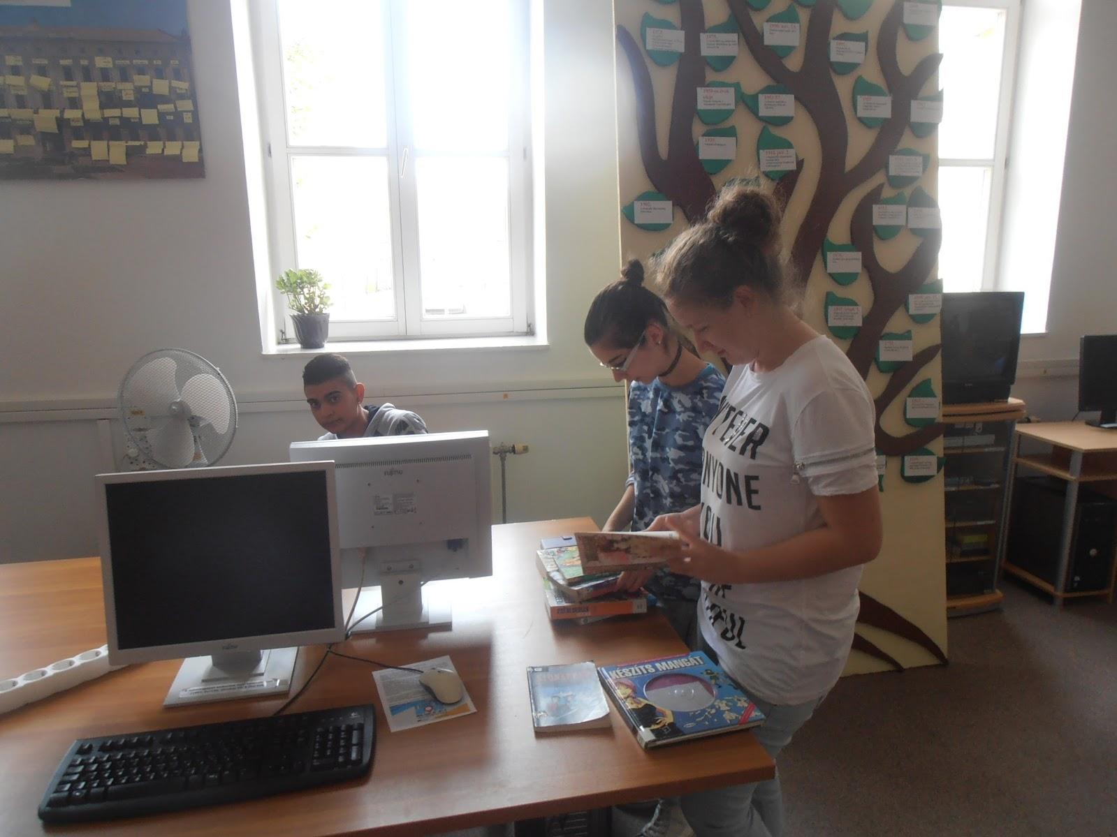 Középiskolás gyerekek könyvet lapozgatnak