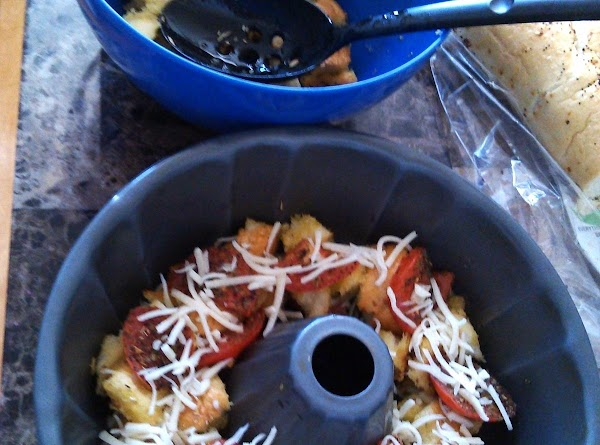 Into a bundt pan, layer bread, tomatoes and cheese, drizzling a little olive oil...