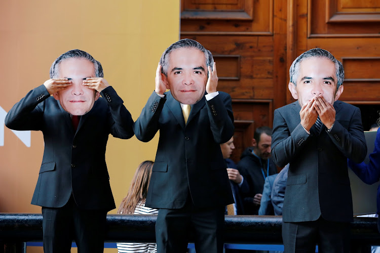 Greenpeace activists gesture while wearing masks of Mexico City's mayor Miguel Angel Mancera during a protest outside the museum holding the Women4Climate conference in Mexico City.