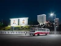 trollybus op groot plein bij avond met 2 grote, verlichtte, borden met de portretten van 2 grote leiders. Enkele mensen staan in grote kring in de verte op het plein