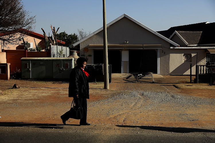 A pedestrian walks past the vandalised gate at the Myne Maatjies day-care centre on August 23 2019.