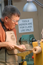"Photo: Ernie starts his demonstration with a jam chuck tapped to screw onto the lathe spindle.  He shows the use a ""turning arm"" as an accessory tool rest to hold his scraper to true up the face of the jam chuck.  Then he worked on making the hole just the right size for the blank."