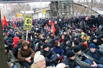 Menschenmenge, sitzend. Plakat: «Gegen Nazis», rote Fahnen.