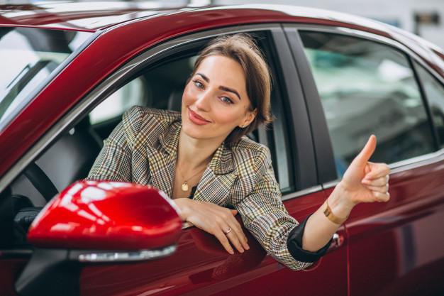 Mulher, sentada no assento do motorista, acenando de dentro de um dos melhores carros usados, na cor vermelha.