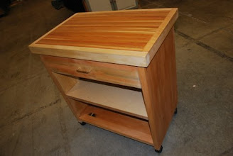 """Photo: This is our medium sized Kitchen Cabinet the perfect size when our small is too small but our large kitchen cart is just too big. With a maple and cherry cutting board top, this works great for all those kitchen projects. The 6.5"""" drawer right is great for keeping your chopping utinsils handy. With a Lifetime structural guarantee. Northwest Cedar with a natural Eucalyptus inlay and Birch sides. Built with the strongest lightweight Eco-Friendly furniture ever invented, guaranteed! Style: Contemporary Size: 31"""" Wide 32"""" Tall 20"""" Deep Drawer Size: 30"""" Wide 9"""" High 17""""Deep Color: Natural Wood Veneer"""