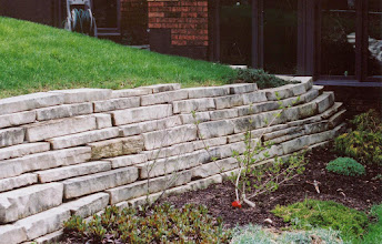 Photo: This curving stone wall accentuates the topography of the garden and backs the plantings, showing them off beautifully.