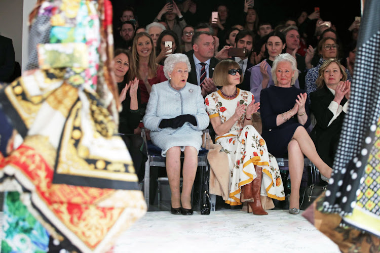 Queen Elizabeth II sits with Anna Wintour as they view Richard Quinn's runway show during London Fashion Week on February 20 2018.