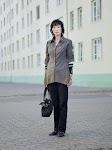 staande Koreaanse vrouw voor wit gebouw
