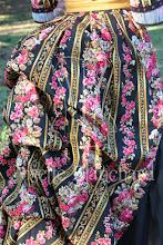Photo: Vestido vitoriano tardio de passeio aproximadamente da década de 1870, em algodão estampado floral e tricoline preto com saia em babados de cetim dourado.  A partir de R$ 400,00.  Underwear: Chemise e bloomer em algodão preto, corset midbust em brocado preto ( ref: CRM 1890 02), bustle em aço e sarja e petticoat em algodão com babados.  Cada figurino é único e exclusivo!