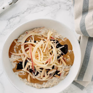 Almond Butter & Jelly Oatmeal Bowl with Spiralized Apples and Toasted Almonds.