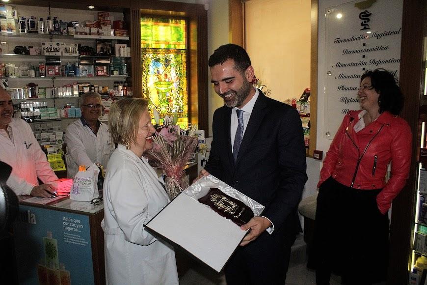 El alcalde hace entrega de una metopa a la farmacéutica María Rosa Morales.