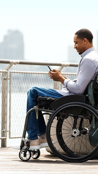 Man in wheelchair using Android phone on a pier