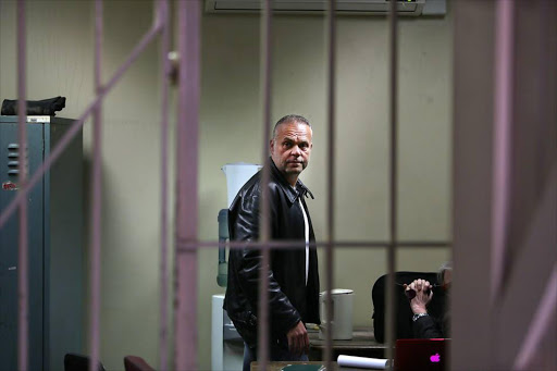 Radovan Krejcir talks to his lawyer in the holding cells ahead of his bail application at the Germiston Magistrate's Court in July. The bail application has to do with the murder case of Sam
