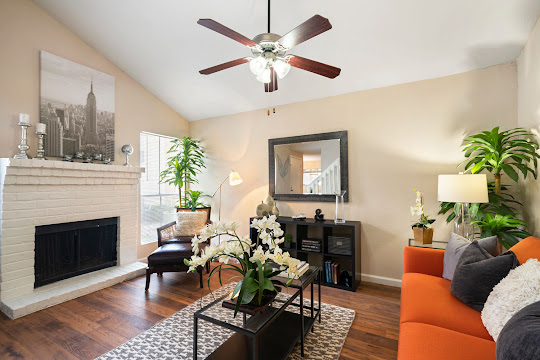 Living room with wood-inspired flooring, tall ceilings with ceiling fan, fireplace, and furniture