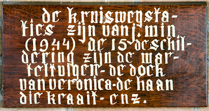 Photo: Uitleg Kruiswegstaties  Wooden sign about the stations of the cross.  The Stations of the Cross  The frescos were painted in 1944 by Jaap Min. The Stations of the Cross consist of 14 different paintings, and the 15th painting shows all the attributes.