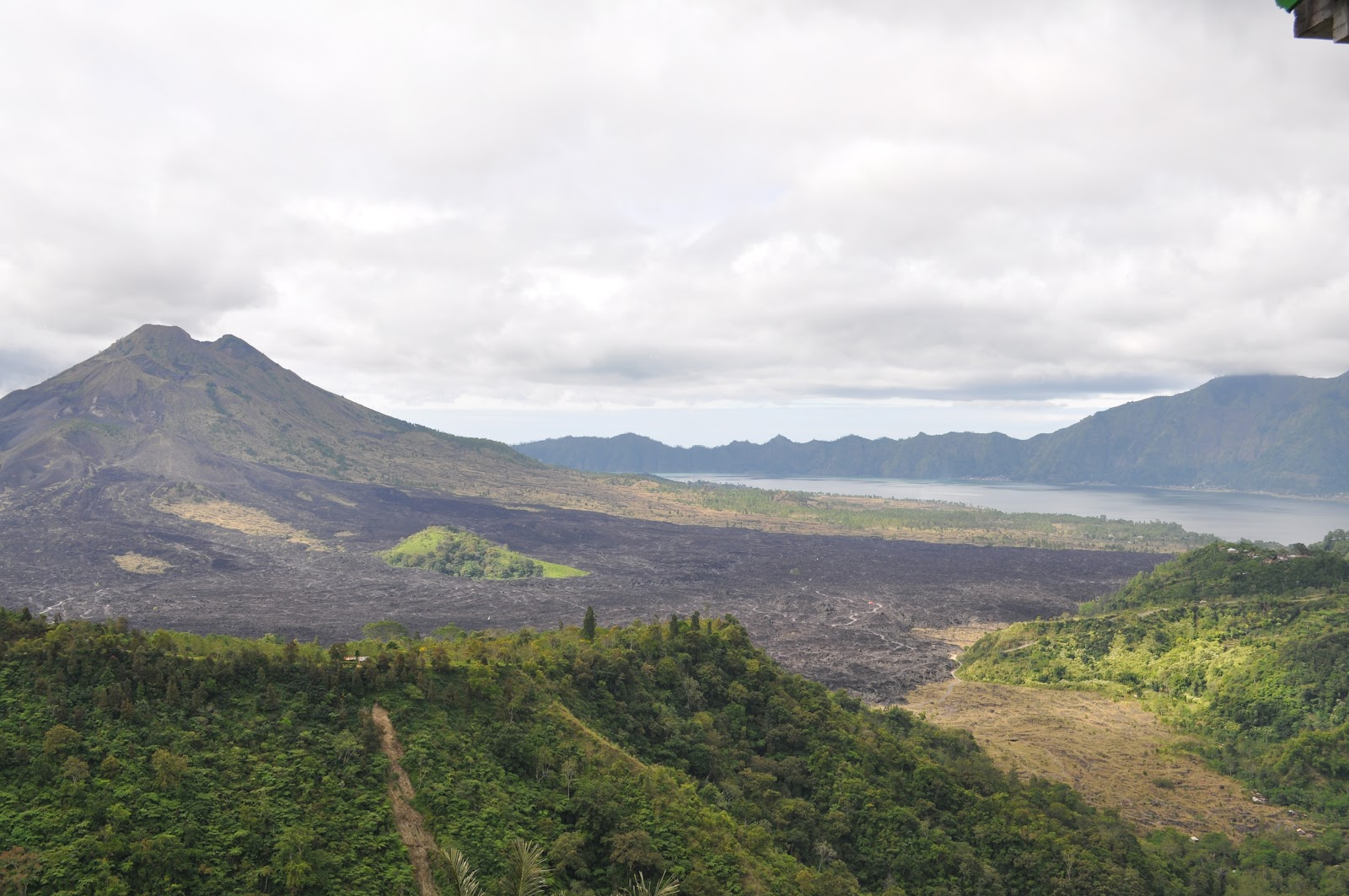 mount batur volcano surrounded by forest and lake batur on a cloudy day in bali indonesia view from sari mountain restaurant