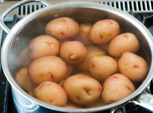 Boil the potatoes in salted water until they're fork tender.