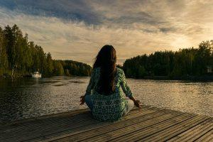 A woman meditating by the lake, which is even more relaxing after moving from Miami to a small town.