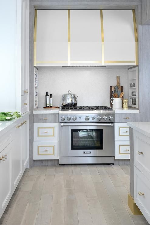 modern white and gold kitchen with brass strap accents on the cabinets and range hood