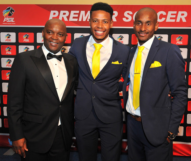 A file photo of Bongani Zungu (C) flanked by his head coach Pitso Mosimane (L) and then assistant coach Rulani Mokoen at the 2015/16 Premier Soccer League Awards ceremony in Johannesburg in May 2016 before the midfielder secured a move to Europe.