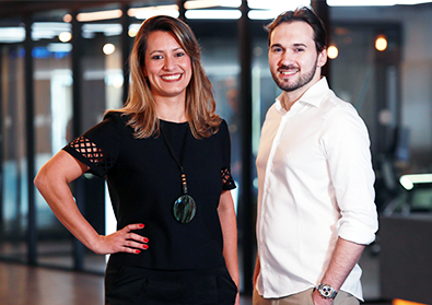 Founders Tatiana and Everton pose in front of an office space