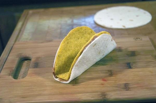 Wrap the flour tortilla around the taco shell.