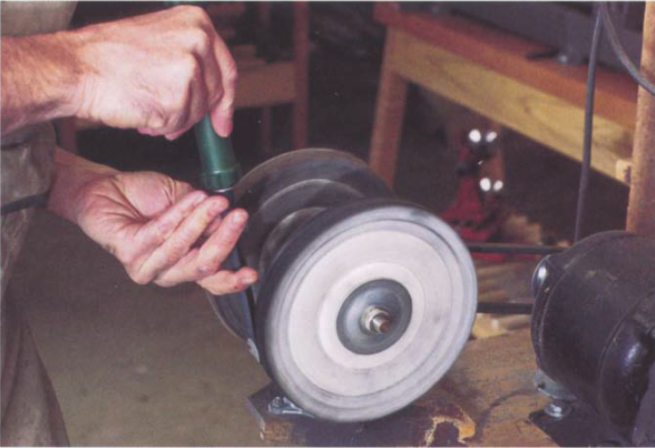 Proper buffing technique when honing a spindle gouge requires you to buff off the edge and to hold the tool tangentially to the wheel.