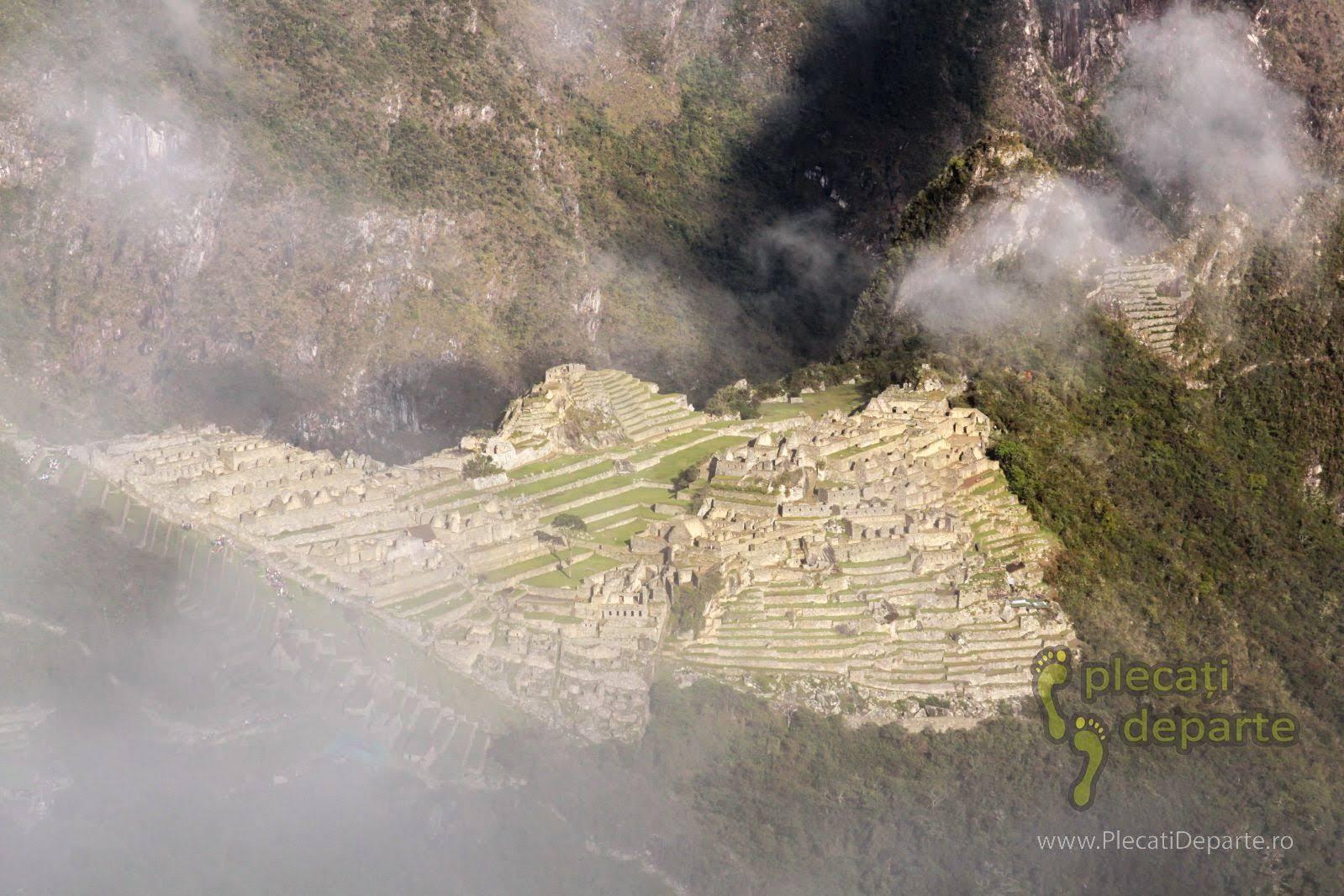 Asezarea incasa Machu Picchu, vazuta printre nori, de sus, de la Poarta Soarelui (Sun Gate), de pe Inca Trail, in Peru