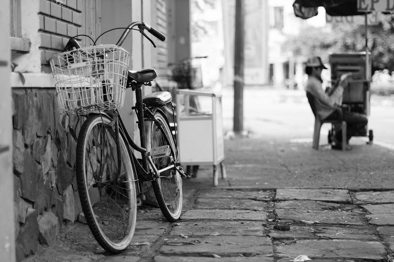 Photo: Motivation Monday - A humble beginning of many businesses I spotted this scene on my walk in Phan Rang, Vietnam. The man sitting in the background is the owner of this bicycle. He's actually tending his kiosk of decal lamination services. May be he'll continue to sit on this corner for many years to come. Or may be he'll accrue enough money through keeping operating cost low and living frugally to open a bigger business. The possibilities are there depending on what he's aiming for.  Please feel free to explore other photos in my #rediscovervietnam series.  #peopleatworkmonday is curated by +Baki Karacay #monochromemonday is curated by +Charles Lupica+Hans Berendsen+Jerry Johnson+Manuel Votta+Steve Barge #phanrang  #vietnam  #bicycle  #motivationmonday
