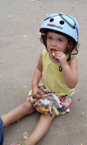 Toddler girl wearing a bike helmet while eating a snack