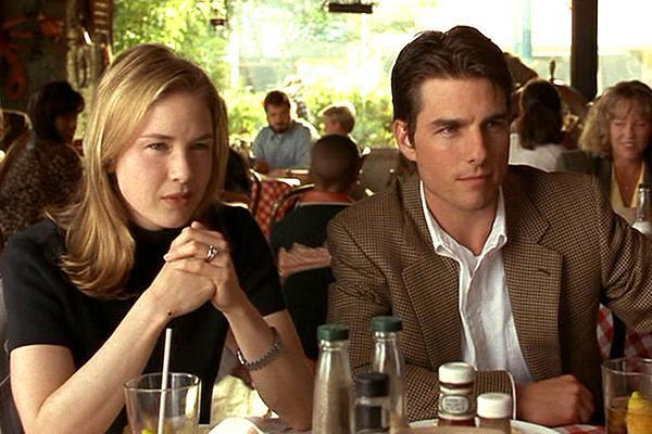 homem de terno e mulher de camiseta preta sentados em mesa de restaurante