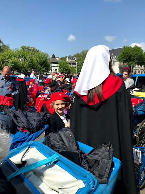 Image: Young girl wearing a red beret standing next to a blue cart, smiling at the camera. Other figures in black and red have their backs turned.