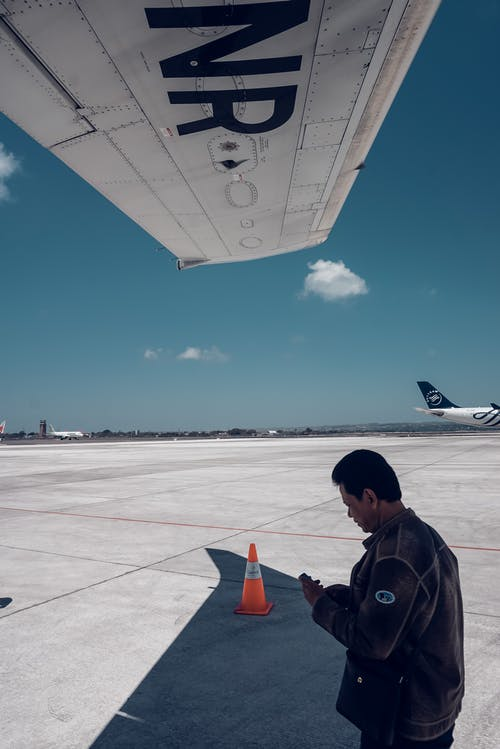 Ethnic man standing near aircraft on sunny day