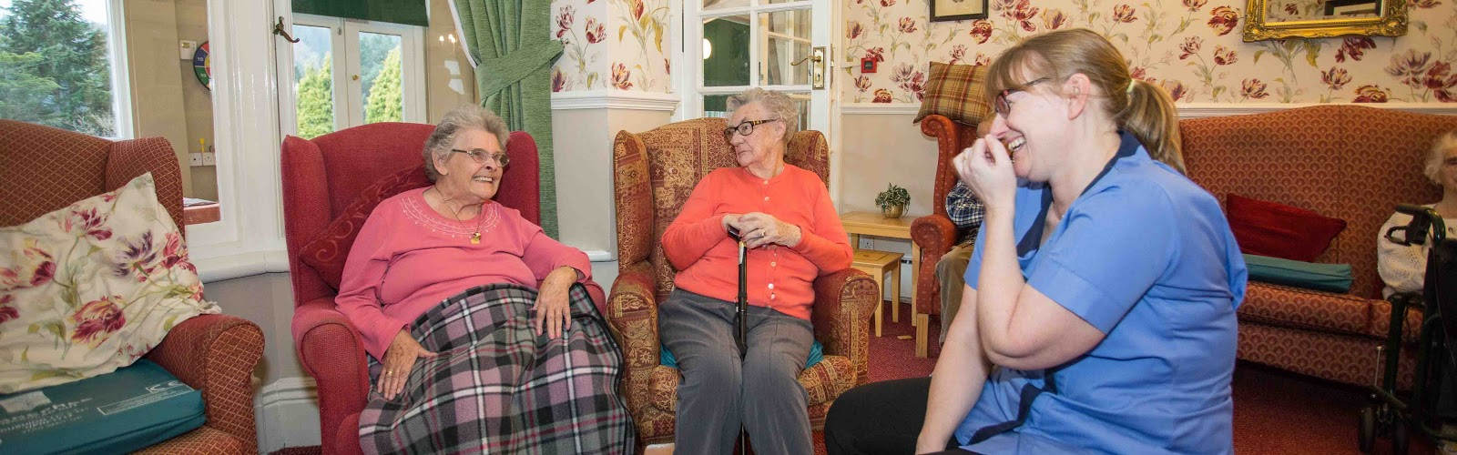 Two elderly ladies enjoying their time with a carer