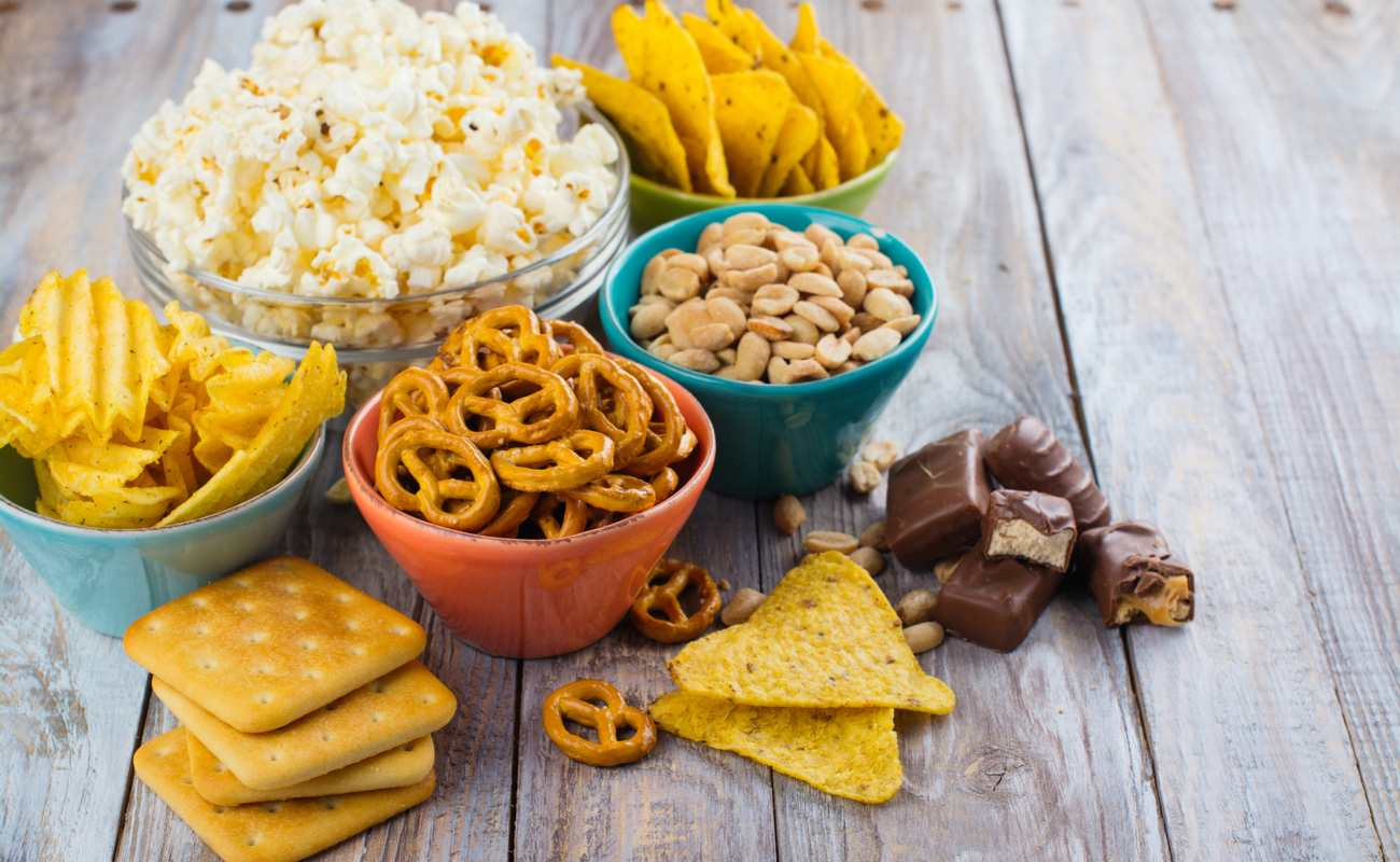 Different types of snacks on a wooden surface