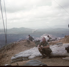 Photo: Jim Hackett on LZ Peanuts sitting on sleeping hootch shared with Charles Brown.  Suspect Hill 400 roughly 1 km in distance.