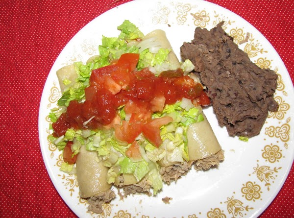 Lay tortilla in plate and spoon a tablespoon or two of chicken into center...