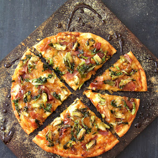 Pizza with Caramelized Onions Prosciutto Kale Sprouts and Balsamic Drizzle