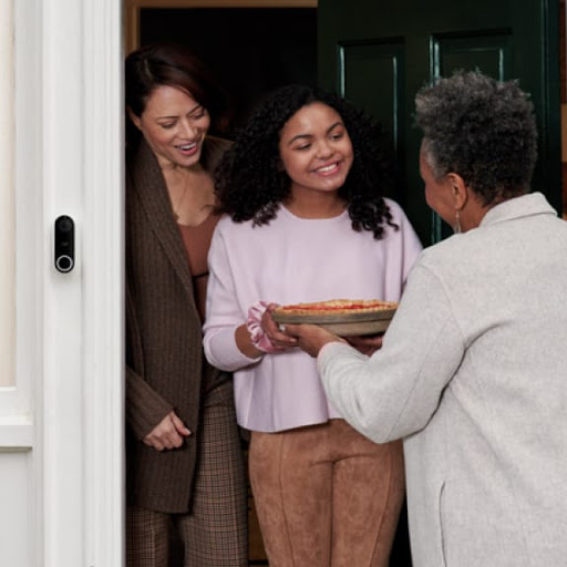 A neighbour or friend drops off a gift to the front door of a family.