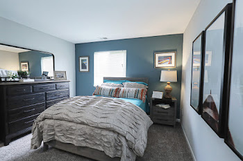Model bedroom with brown carpet, blue accent wall, and large bed with neutral bedding